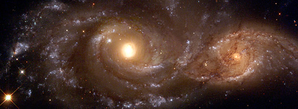 Strong tidal forces from the larger galaxy, cataloged as NGC 2207 (left), have distorted the shape of the smaller one, IC 2163 (right), flinging out stars and gas into long streamers stretching out a hundred thousand light-years. (copyright GRIN)